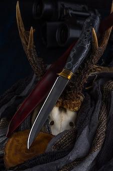 Faca de caça artesanal feita de aço damasco repousa sobre os chifres
