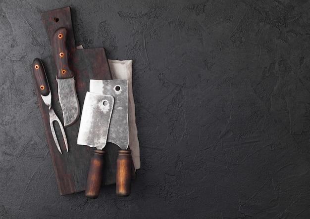 Faca de carne vintage e garfo e machadinhas com tábua vintage e mesa preta.