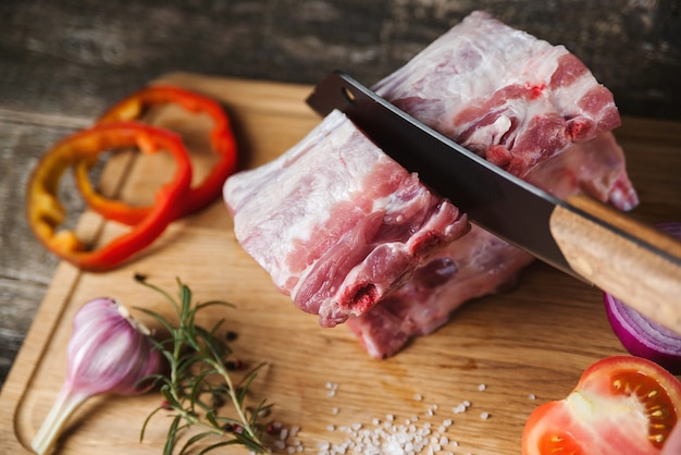 Faca de cortar carne de açougueiro e especiarias na placa de madeira. vista superior de costela de porco fresca crua com especiarias.