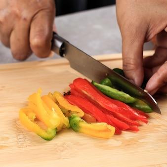 Faca de corte de pimenta e tábua de cortar de madeira com pimentão amarelo verde vermelho