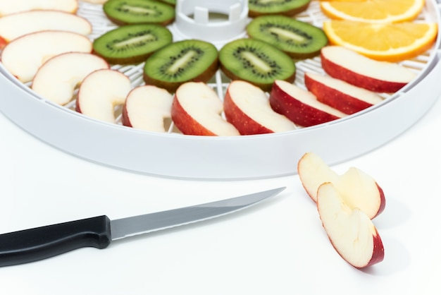 Faca de cozinha e maçã cortada. atrás está uma bandeja com desidratador com fatias de kiwi e maçãs.