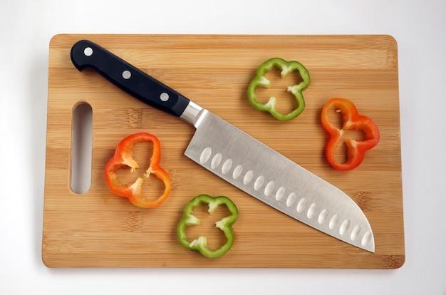 Faca de cozinha universal com uma lâmina como santoku em uma tábua de cortar