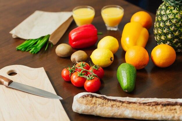 Faca de frutas de legumes frescos e tábua de cortar para cozinhar o jantar em madeira