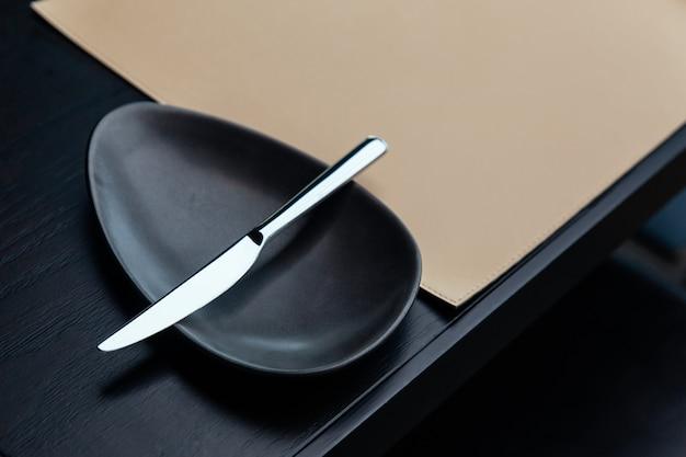 Faca de manteiga de prata na bacia preta na tabela de madeira com esteira de couro.