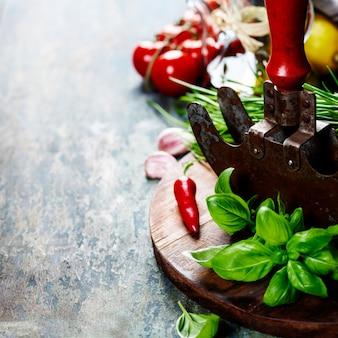 Faca de mezzaluna de corte de ervas vintage e ingredientes frescos