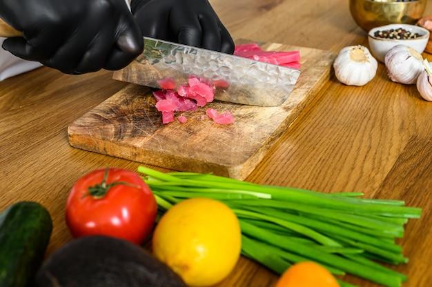 Faca de sashimi do chef japonês, corte o atum cru para cozinhar o tártaro.