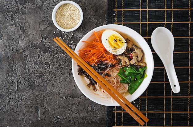 Faça dieta a bacia do vegetariano de sopa de macarronete de cogumelos de shiitake, cenoura e ovos cozidos. comida japonesa. vista do topo. lay plana