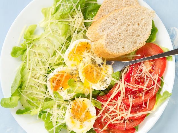 Faça dieta a salada com ovos cozidos, queijo e vegetais macios - tomates, alface.