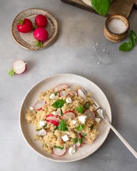 Faça dieta a salada com quinoa, queijo feta, rabanete e manjericão em um prato de cerâmica. conceito de comida saudável.