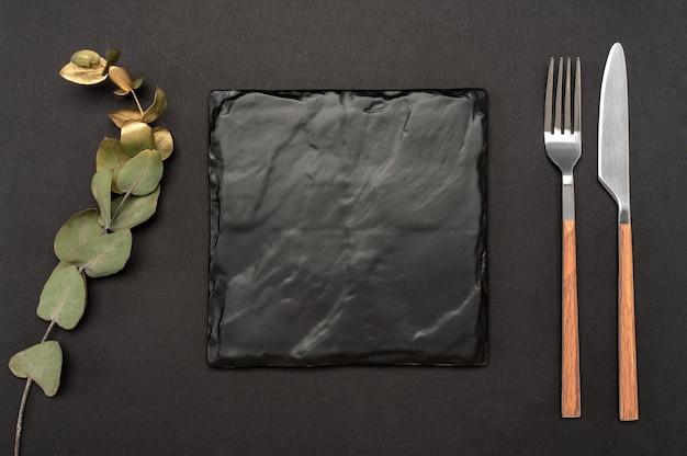 Faca e garfo com quadro quadrado de ardósia preta para o texto do menu ou receita e galho de ouro de eucalipto na mesa preta