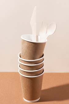 Faca e garfo de papelão em uma pilha de copos