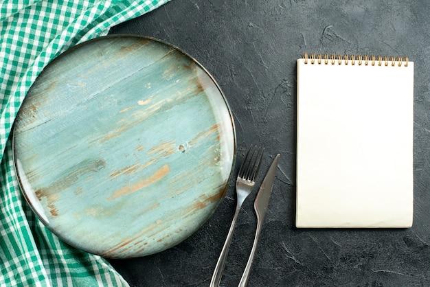 Faca e garfo em mesa preta com toalha de mesa, prato redondo, vista superior