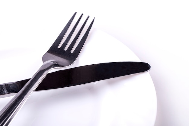 Faca e garfo no prato vazio em um branco
