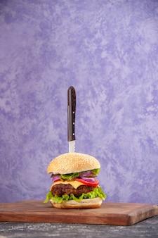 Faca em um delicioso sanduíche de carne em uma tábua de madeira na superfície de gelo isolada com espaço livre