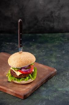 Faca em um saboroso sanduíche de carne em uma tábua de madeira em uma superfície escura isolada com espaço livre