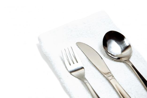 Faca, garfo e colher com guardanapo de linho, isolado no branco