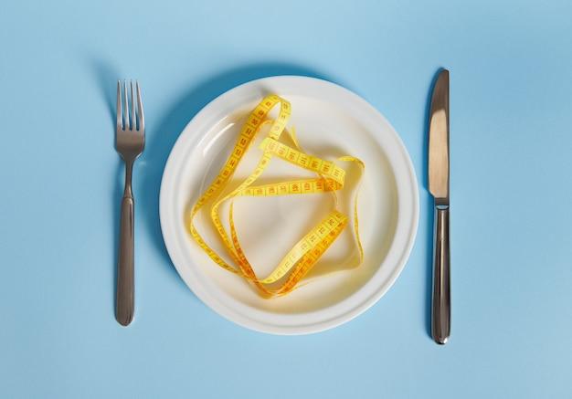 Faca, garfo e fita métrica em um prato vazio. conceito de dieta