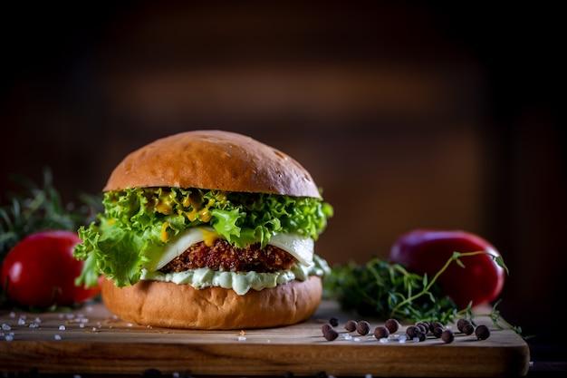 Faça hambúrguer de frango crocante com queijo, alface, tomate e molho no fundo de madeira