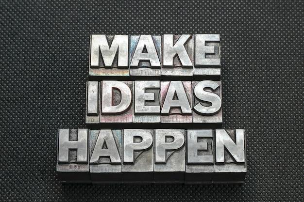 Faça ideias acontecerem, frase feita de blocos de impressão tipográfica metálicos em superfície preta perfurada