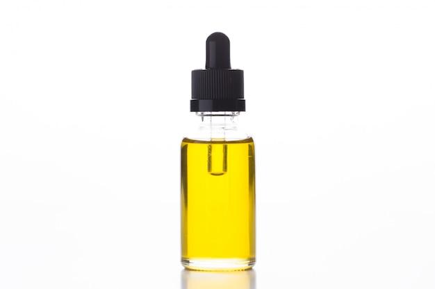 Faça massagens o óleo em uma garrafa de vidro com uma pipeta no branco isolado.