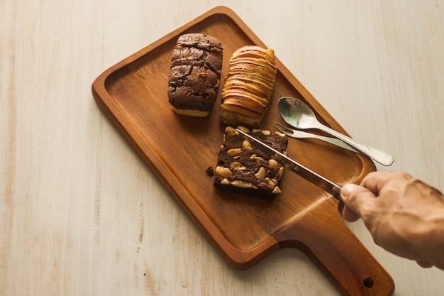 Faca na mão pronta fatia brownie de padaria na bandeja de madeira