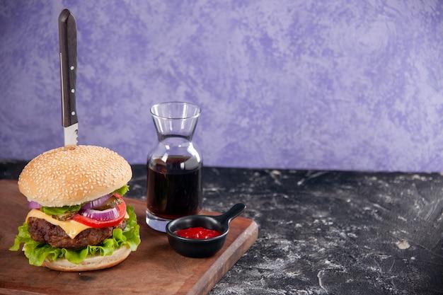 Faca no saboroso sanduíche de carne com molho de ketchup na tábua de madeira do lado direito na superfície isolada do gelo