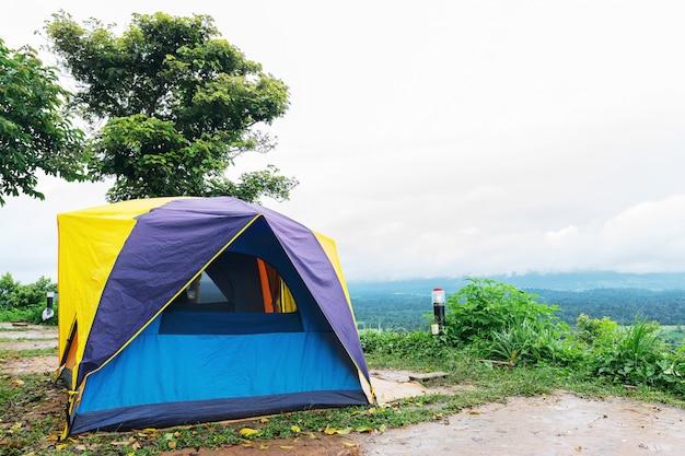 Faça o close up de uma barraca de camping montada no ponto mais alto de uma alta montanha com céu e montanhas ao fundo