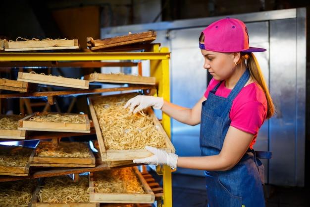 Faça o macarrão. fábrica de massas. produção de espaguete. massa crua. trabalhador com uma caixa de macarrão. menina trabalha na produção de macarrão