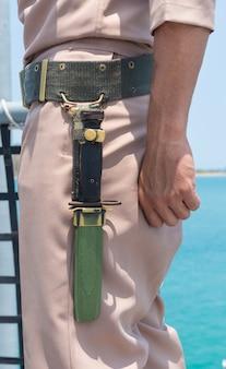Faca perto da mão do marinheiro lateral na vista para o mar do navio exterior.