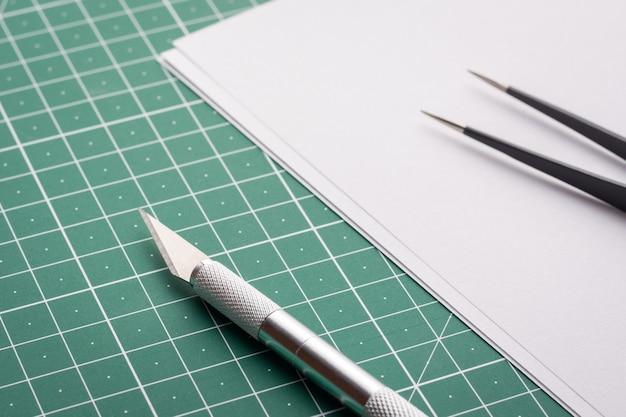 Faca profissional e pinça perto de papel branco em branco na esteira de corte