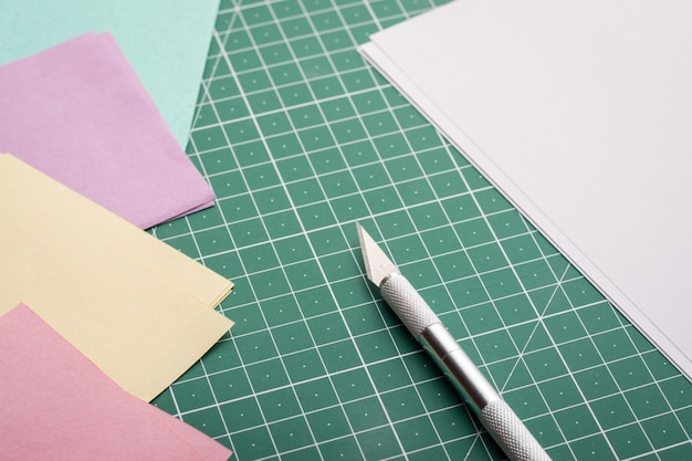 Faca profissional perto de papel branco em branco e diferentes papéis coloridos na esteira de corte