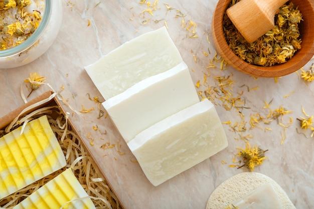 Faça sabonetes artesanais com flores secas de ervas. produtos de banho naturais com flores de calêndula secas para o cuidado da pele do body spa. artigos de higiene pessoal.