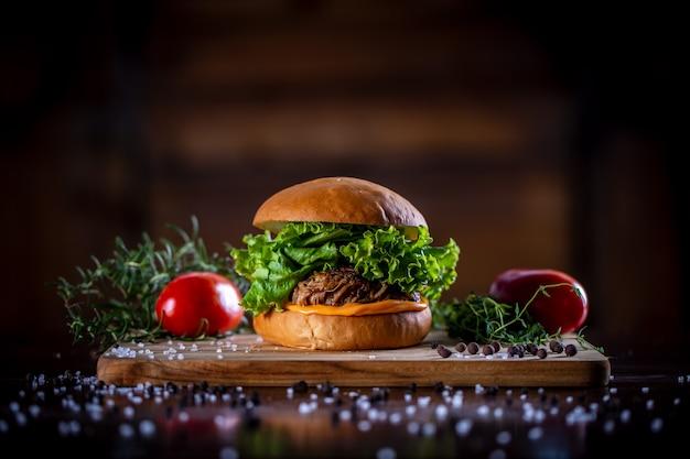 Faça sanduíche de carne de porco com queijo cheddar, alface e cebola roxa em fundo de madeira
