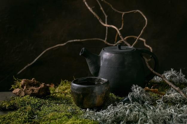 Faça um bule de cerâmica feito à mão sobre musgo como pano de fundo