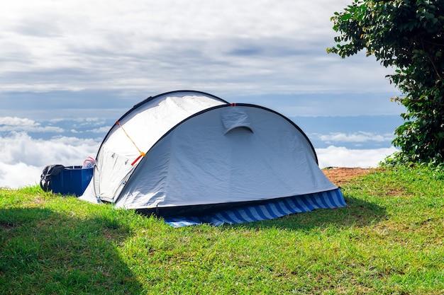 Faça um close de uma barraca de camping montada em um campo gramado no ponto mais alto de uma alta montanha