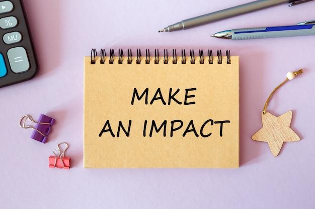 Faça um impacto escrito em um bloco de notas em uma mesa de escritório com acessórios de escritório