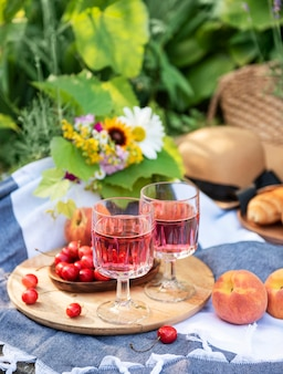 Faça um piquenique ao ar livre em campos de lavanda. vinho rosé na taça, cerejas e chapéu de palha no cobertor
