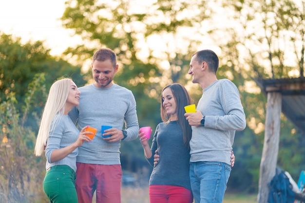 Faça um piquenique com os amigos junto à lareira. amigos da empresa tendo um fundo de natureza de piquenique de caminhada. amigos contam histórias. piquenique de verão. divirta-se com os amigos