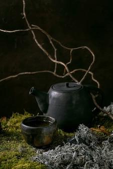 Faça uma chaleira de cerâmica artesanal e uma xícara wabi-sabi de chá verde quente sobre musgo com galhos secos e folhas. cerimônia do chá de natureza outonal.