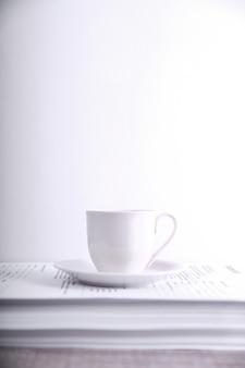 Faça uma pausa para beber café conceito. xícara de café em uma pilha de papel em cima da mesa