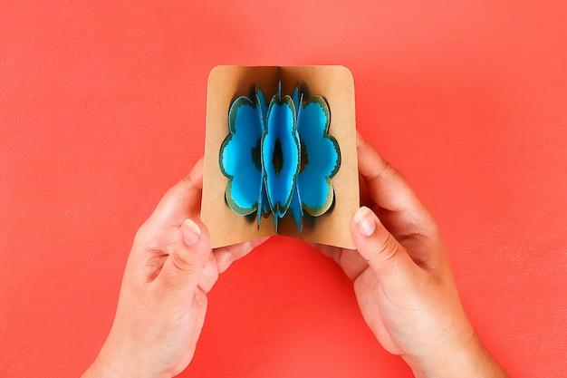 Faça você mesmo o cartão 3d tridimensional com as flores para o dia de mães em um fundo coral vivo.