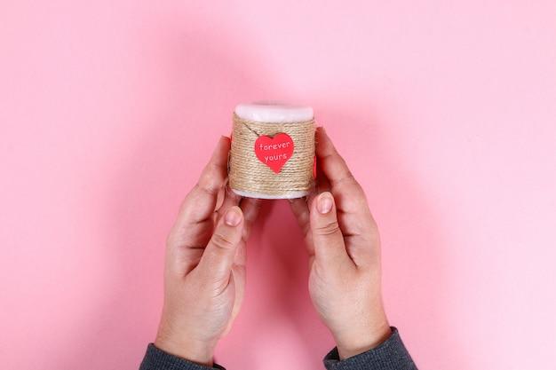 Faça você mesmo. vela para o dia dos namorados. mãos de decoração para 14 de fevereiro de velas, cordéis e corações.