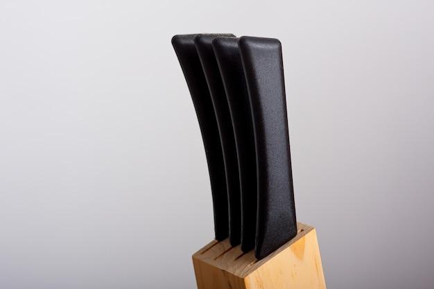 Facas com cabos pretos colocadas em um suporte para facas