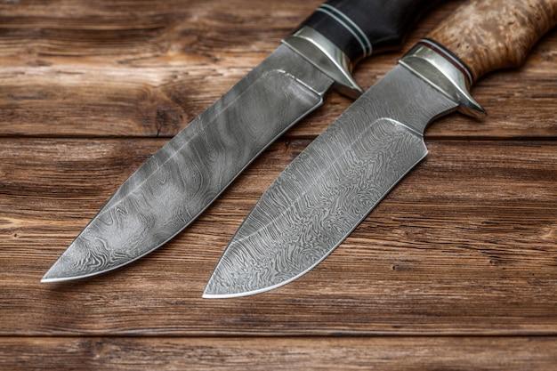 Facas de aço damasco caça artesanal na superfície de madeira