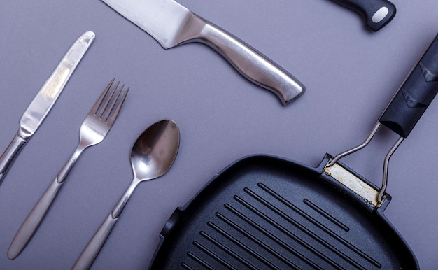 Facas de metal com preto sobre uma mesa cinza, grill pan