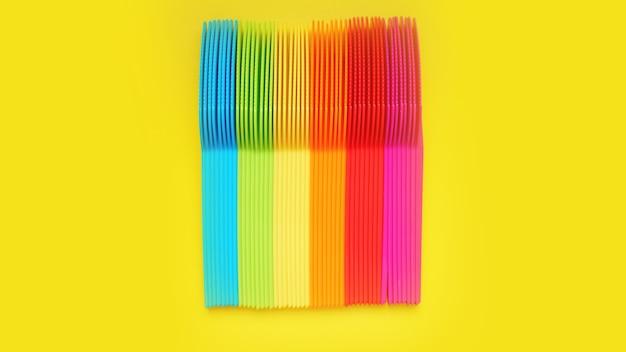 Facas de plástico violeta, laranja, amarelo, azul, vermelho isolado na superfície amarela - conceito de verão brilhante para design e banners