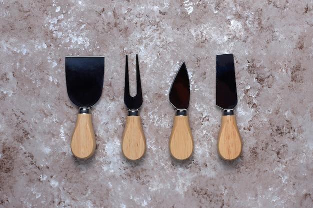 Facas de queijo com alças de madeira, garfo, espátula na superfície marrom clara.