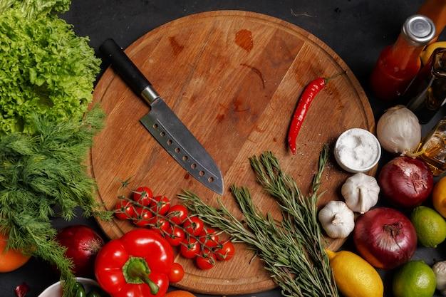 Facas em uma placa de madeira. composição de vários produtos para cozinhar. vista do topo.