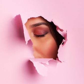 Face da bela adormecida da mulher nova através do fundo de papel cor-de-rosa do espinho.