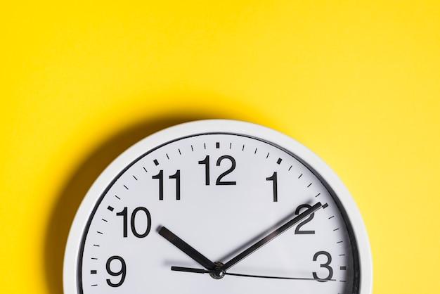 Face do relógio redondo contra pano de fundo amarelo